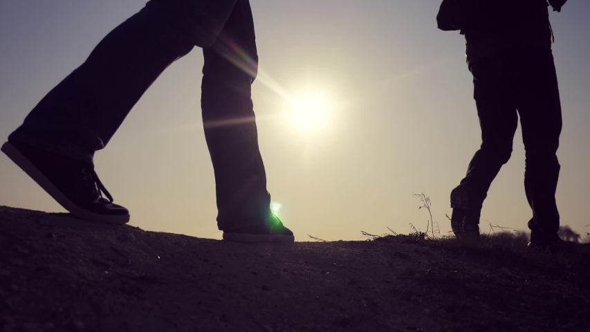 teamwork business travel concept. legs silhouette group hikers of lifestyle people walking on the top of the mountain with backpacks sunset sun light. slow motion video. campaign tourists with #1030475585