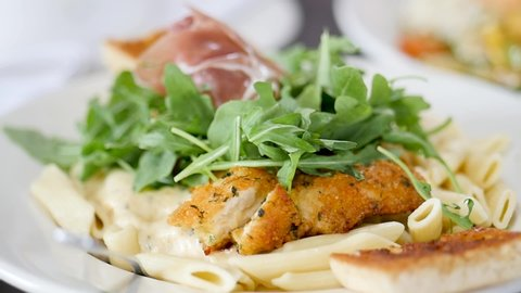 move from chicken dish to salmon dish. The camera moves from one beautiful healthy food plate to another. The first dish is a pasta, chicken & arugula plate. The camera then slowly moves to a salmon.