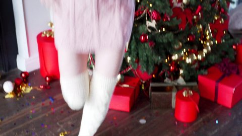 View from toes to head of blonde woman in warm skirt and stockings dancing and having fun. Christmas decorations