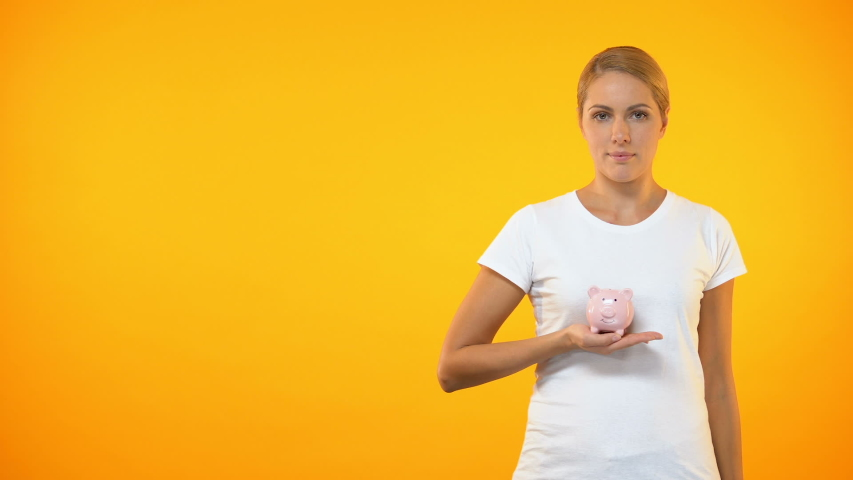 Happy female covering piggybank by hand, safe bank deposit, account insurance   Shutterstock HD Video #1030538045