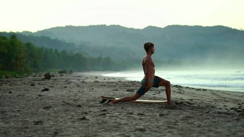 Slow-motion steady cam shot of attractive young fit surfer going doing yoga exercise on the beach. Millennial summer lifestyle, healthy living, sport & travel.