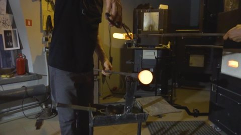 Glassblower taking the rod with liquid glass out of glowing hot oven in his workshop .