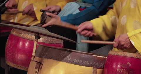 Vietnamese musicians play national ancient instruments in the theater. the musicians are dressed in bright yellow clothes. in the frame of the hands of musicians and musical instruments.