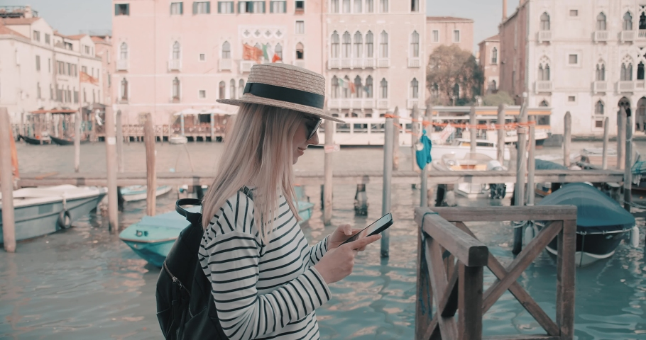 Slow Motion 4K view on Woman tourist Traveler in white sunhat walking and shooting with her phone camera on old streets with canals in Venice, Italy. Girl traveling to famous popular landmark   Shutterstock HD Video #1030673885