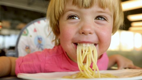 Cute healthy preschool kid boy eats pasta noodles sitting in nursery cafe. Happy child eating healthy organic and vegan food in restaurant. Childhood, health concept