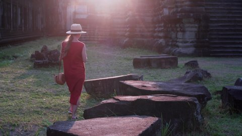 Woman in red dress is walking among ruins of Angkor Wa temple and taking photo of its tower. Sunset. It was built by khmer civilization in 12th century. Cambodia