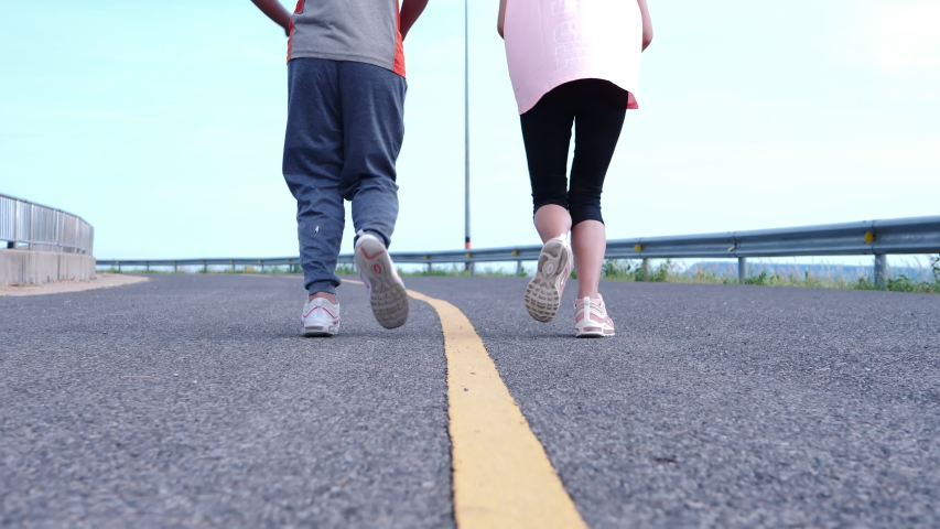 Young Asian couples jogging on the street in the morning. Wind turbines in background. Runing exercise slow Motion, Health care lifestyle. Bottom view #1030682795