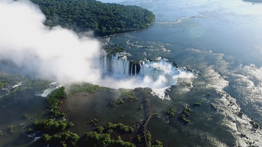 The Iguazu Falls are waterfalls of the Iguazu River on the border of Argentina and Brazil. They are the largest waterfalls system in the world. (aerial photography)   Shutterstock HD Video #1030691465