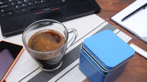Hand puts lot of sugar in cup of hot coffee on table with black laptop, notepad and pens in office. Concept of getting diabetes at break time