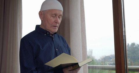 An old muslim man reading Koran