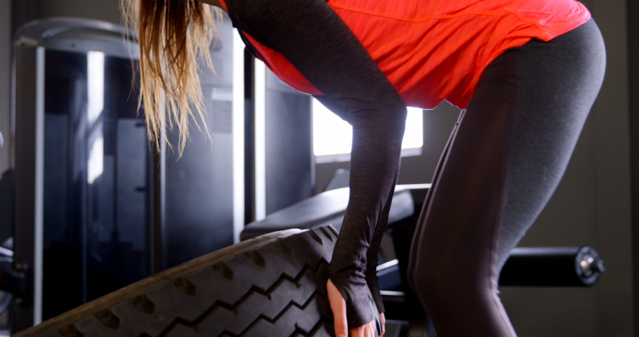 Side view of determined beautiful Caucasian woman exercising in a fitness studio. She is using tyre.  #1030738895