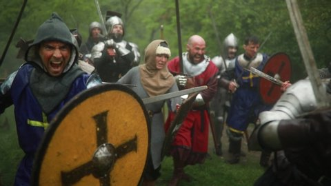Combat squad of medieval knights of the Crusaders stand in armors with their swords and shields and run to attack  against background of misty forest.