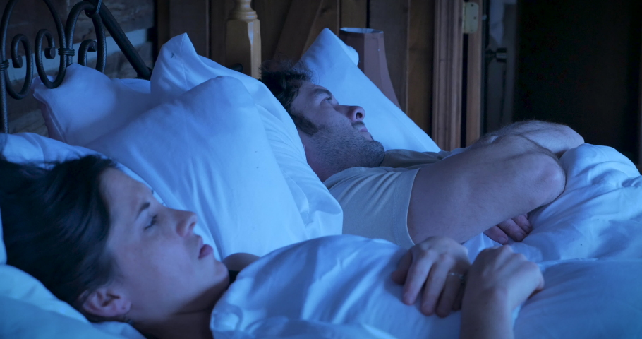 Attractive young woman and man arguing while lying in bed sighing and acting stubborn refusing to give in and communicate with each other at night | Shutterstock HD Video #1030758035
