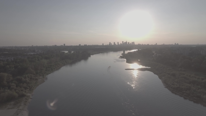 Aerial view of the Vistula River flowing through the city of Warsaw in Poland. The Vistula River is the Golden Hour of the Sunset. Filmed from 4K drone in RAW. Video for post-processing.