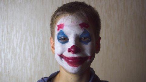 Boy with joker clown makeup on Halloween