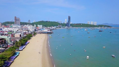 Aerial view of boats in Pattaya sea, beach, and urban city with blue sky for travel background. Chonburi, Thailand.