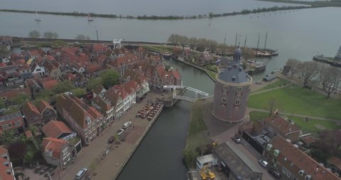 Aerial circling the Drommedaris Defence tower in historic Dutch town Enkhuizen in North Holland the Netherlands with Dutch flag flying traditional houses and rooftops in the background