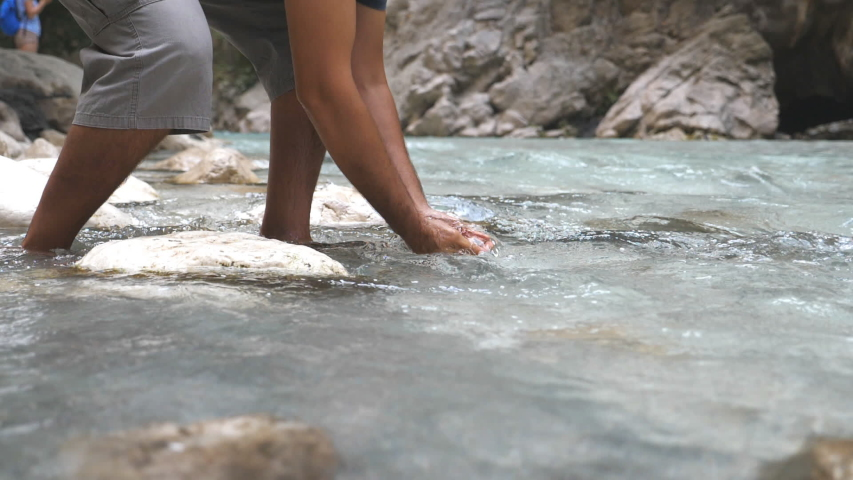 Unrecognizable man washing his hands in mountain river with clear cool water. Guy standing among river with fast stream and refreshing. Male hiker during his travelling. Slow mo Bottom view Close up #1030894565