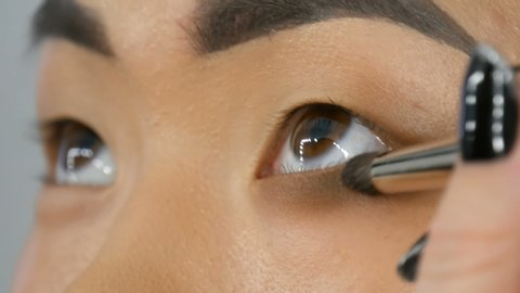 Professional make-up artist makes eye makeup of Korean girl Asian woman with a special brush