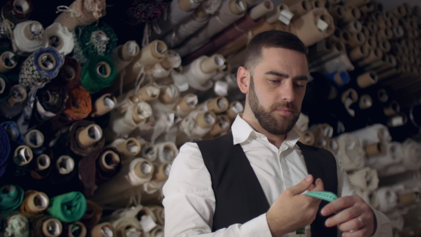 Close up portrait of serious fashion tailor rolling centimeter at work place. | Shutterstock HD Video #1030925225