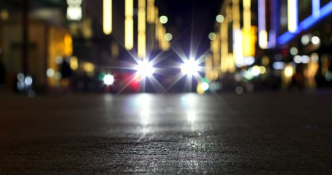 Front view of bokeh of car lights on street at night. Cars are halt at traffic signal