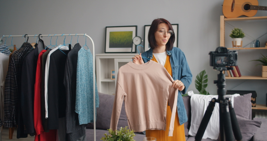 Stylish young woman vlogger is recording video for online blog about trendy clothes holding garment talking and gesturing. Vlogging, people and house concept. | Shutterstock HD Video #1030945055