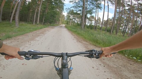 Riding enduro mountain bike on rocky path road between green fields. View from first person perspective POV. 4K gimbal stabilized video, Gopro Hero 7 black.
