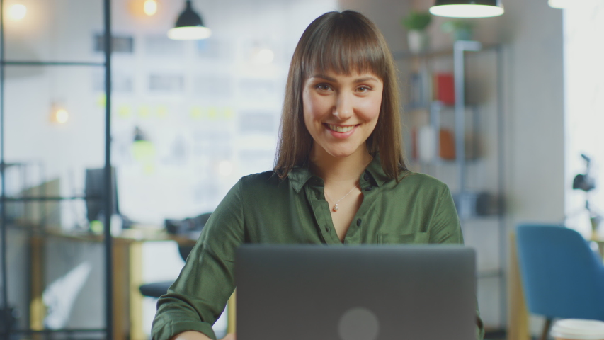 Young Beautiful Brunette Works on a Laptop Computer in Cool Creative Agency in a Loft Office. She Drinks Take-away Coffee. Camera Zooms In and She Smiles and Laughs. | Shutterstock HD Video #1030955375