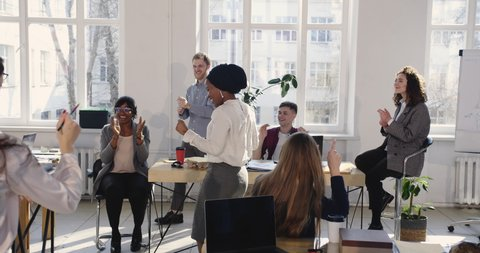 Happy African business woman in ethnic turban doing fun crazy success celebration dance at modern loft office workplace.