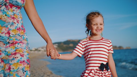 Close up: happy cute daughter with colorful braids, dressed in striped dress holding hand of her mother, walking on beach along coastline. 4k slow motion.
