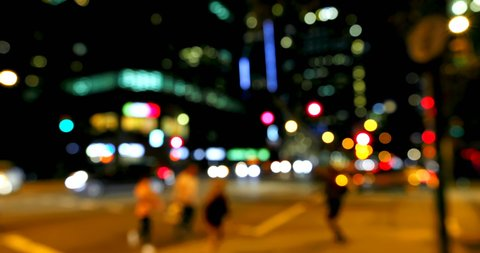 Front view of colorful bokeh of car lights at traffic signal on street at night. Pedestrians crossing street