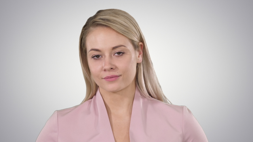 Young beautiful lady in pink looking to camera and thinking of something smiling slightly on gradient background. | Shutterstock HD Video #1031214095