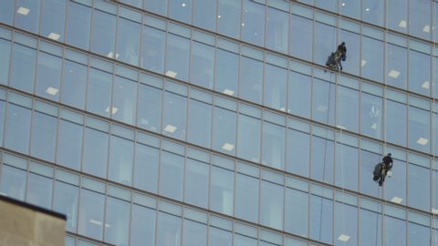 Camera tilts down a high rise building to see two window cleaners cleaning the windows