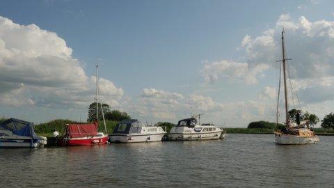 Broads National Park Landmark, Norfolk - June 2019. Family sailing a traditional broads cruiser. The Staithe, River Thurne, Broads National Park, Norfolk, England, United Kingdom