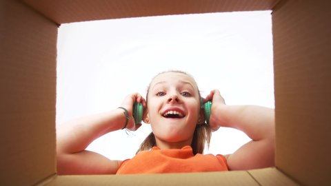 presents, delivery and surprise concept - happy surprised girl taking headphones out of gift box and putting them on