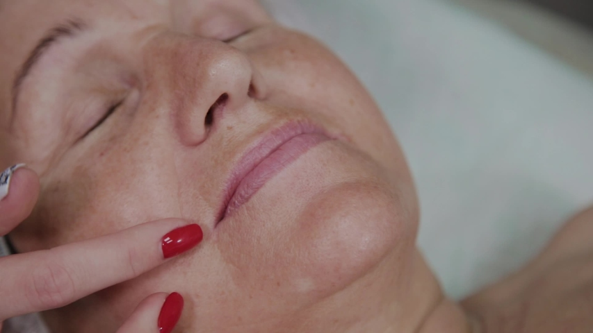 Beautician removes makeup to an elderly woman in a cosmetology clinic. | Shutterstock HD Video #1031266205