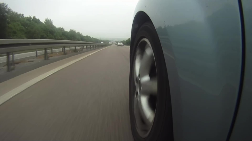 A highly stylized clip of a car speeding down the highway on the German autobahn. Highway wheel ungrade.d | Shutterstock HD Video #1031357585