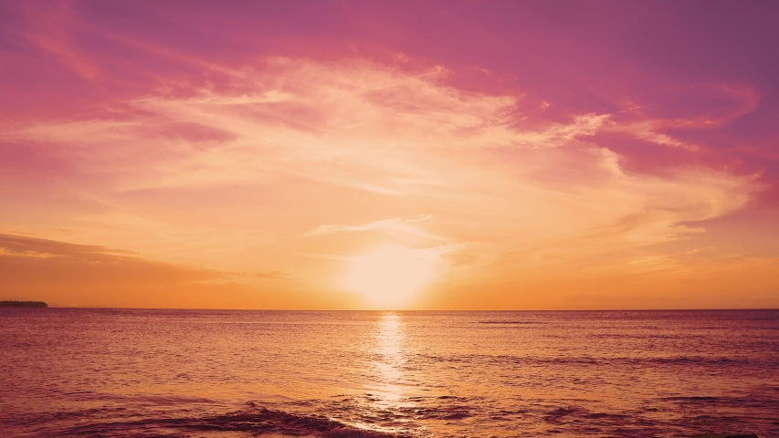 Red sunsets over sea video 4K. The sun touches horizon. Red sky, yellow sun and amazing sea. Summer sunset seascape. Atlantic Ocean beach sunsets. The sun in spindrift clouds Fantastic natural sunsets