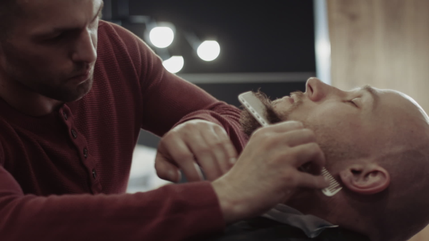 Barber shaving beard with electric razor and comb in a barbershop. Close up of a young barber trimming beard with shaver. A drop of sweat runs down barber forehead | Shutterstock HD Video #1031554925