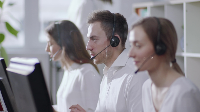 Business and technology concept - helpline operator with headphones in call centre working hard, then looks straight to camera and smiles happily. Politeness, good mood, positive emotions. Female | Shutterstock HD Video #1031614205