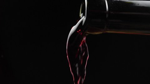 Wine. Red wine pouring from neck of bottle in wine glass over dark background. Rose wine pouring from the bottle. Slow motion