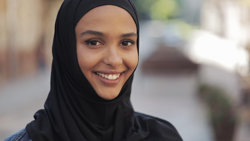 Portrait of beautiful young Muslim woman wearing hijab headscarf smiling into the camera standing on the old city background. #1031650865