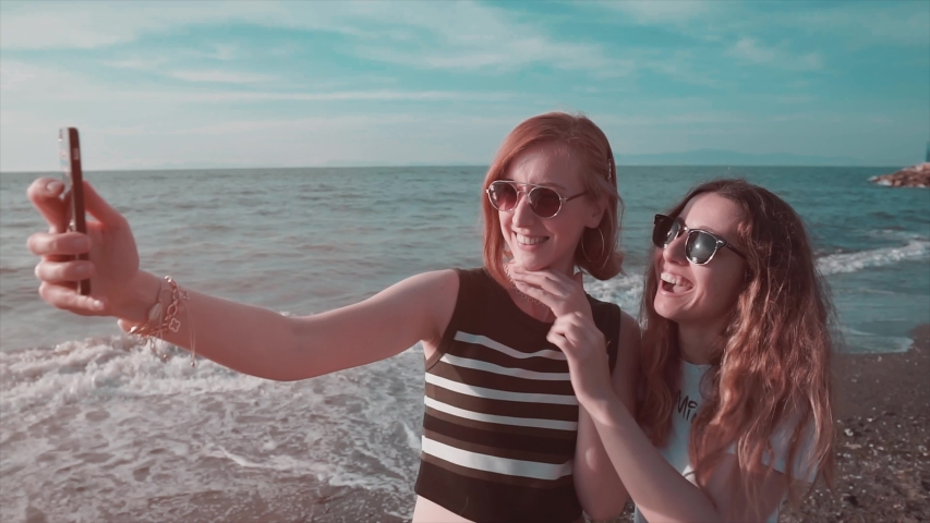 Young girls are taking selfie on beach with sea and sunset. Happy two friend take a photo with mobile phone. | Shutterstock HD Video #1031682755