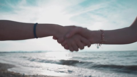 Deal hands, hand shake woman on sand, seaside. Blurry background with empty sea and hand gestures, successful job, tem or partnership agreement outside.