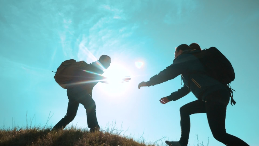 Happy family teamwork help business travel concept. two hikers man and woman tourists climbers climb to the top of the mountain. extends a helping hand overcoming hardships teamwork the path to | Shutterstock HD Video #1031745755