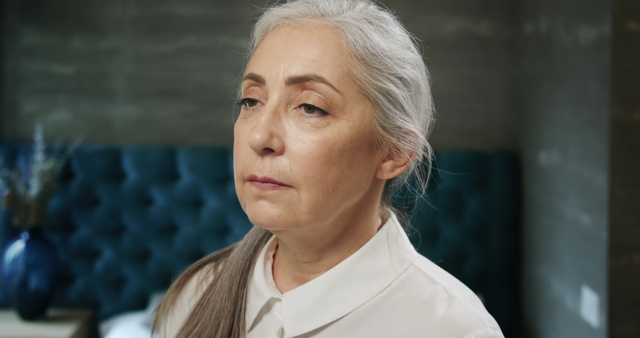 Elegant retired female in white blouse smiling to camera in modern interior   Shutterstock HD Video #1031758025