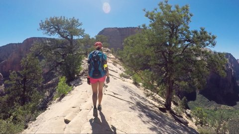 Young woman wearing backpack is walking on the ridge to Angel's Landing in Zion National park in Utah, USA. Female on a hiking trail in Zion National Park in Usa