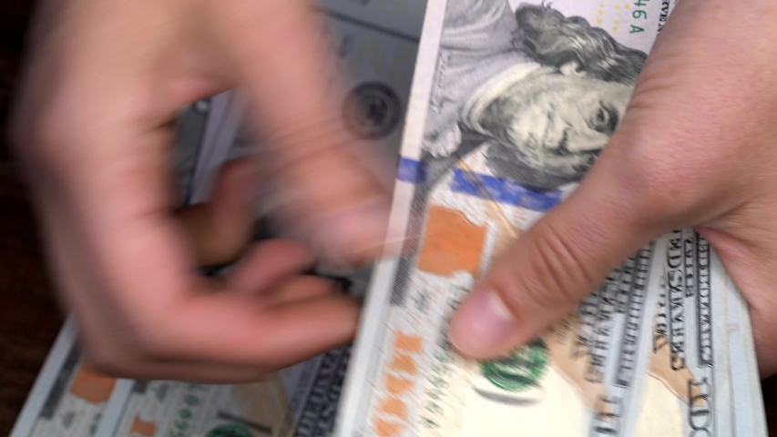 This close up video shows an anonymous pair of caucasian hands counting money from a new stack of hundred dollar bills. | Shutterstock HD Video #1031828855