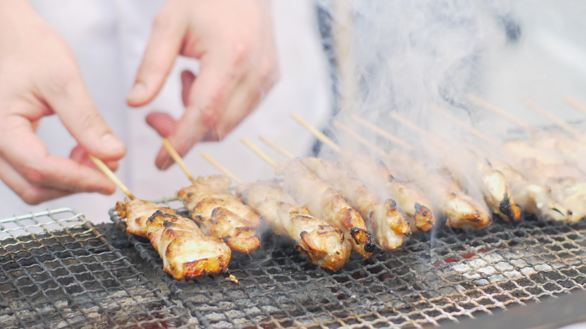 Someone is cooking traditional chicken yakitori (BBQ) in Tokyo street, Japan. Closeup view. Chicken yakitori is famous japanese street food.   Shutterstock HD Video #1031834915