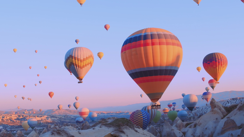 Hot-air balloons flying over the mountain landsape of Cappadocia,Turkey. | Shutterstock HD Video #1031910785